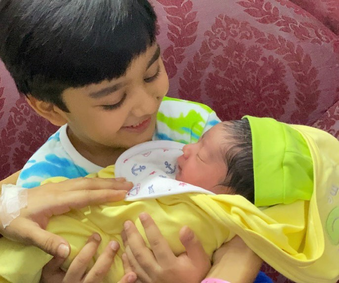 sohaan holding his newborn brother romaan
